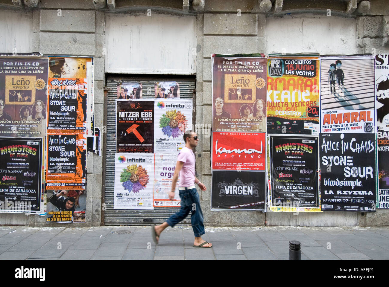 Man walking past fly posters advertising rock bands in Chueca area, Madrid Spain - Stock Image