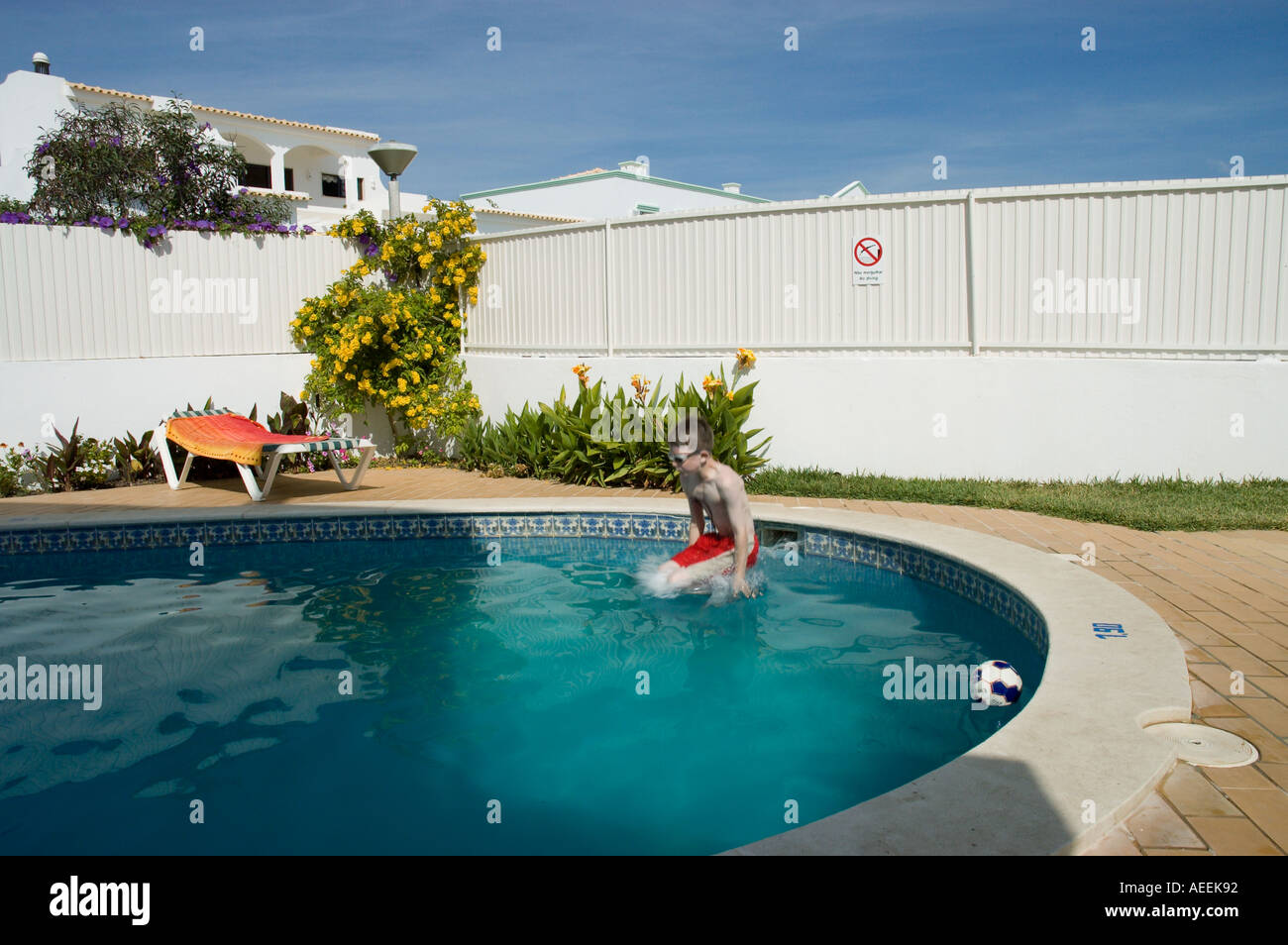 9 year old boy jumping into a swimming pool on holiday Stock Photo