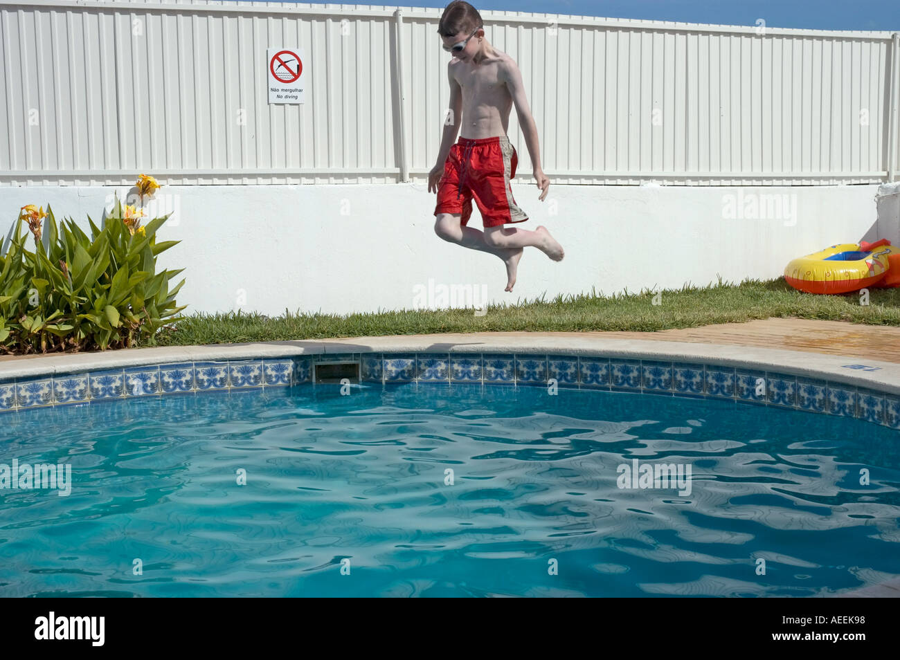 9 year old boy jumping into a swimming pool on holiday - Stock Image