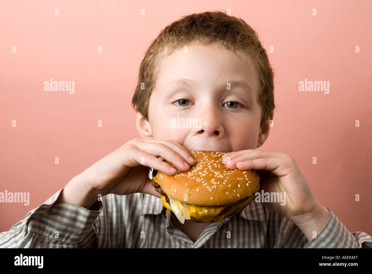 Boy eating McDonald's burger, England, UK - Stock Image