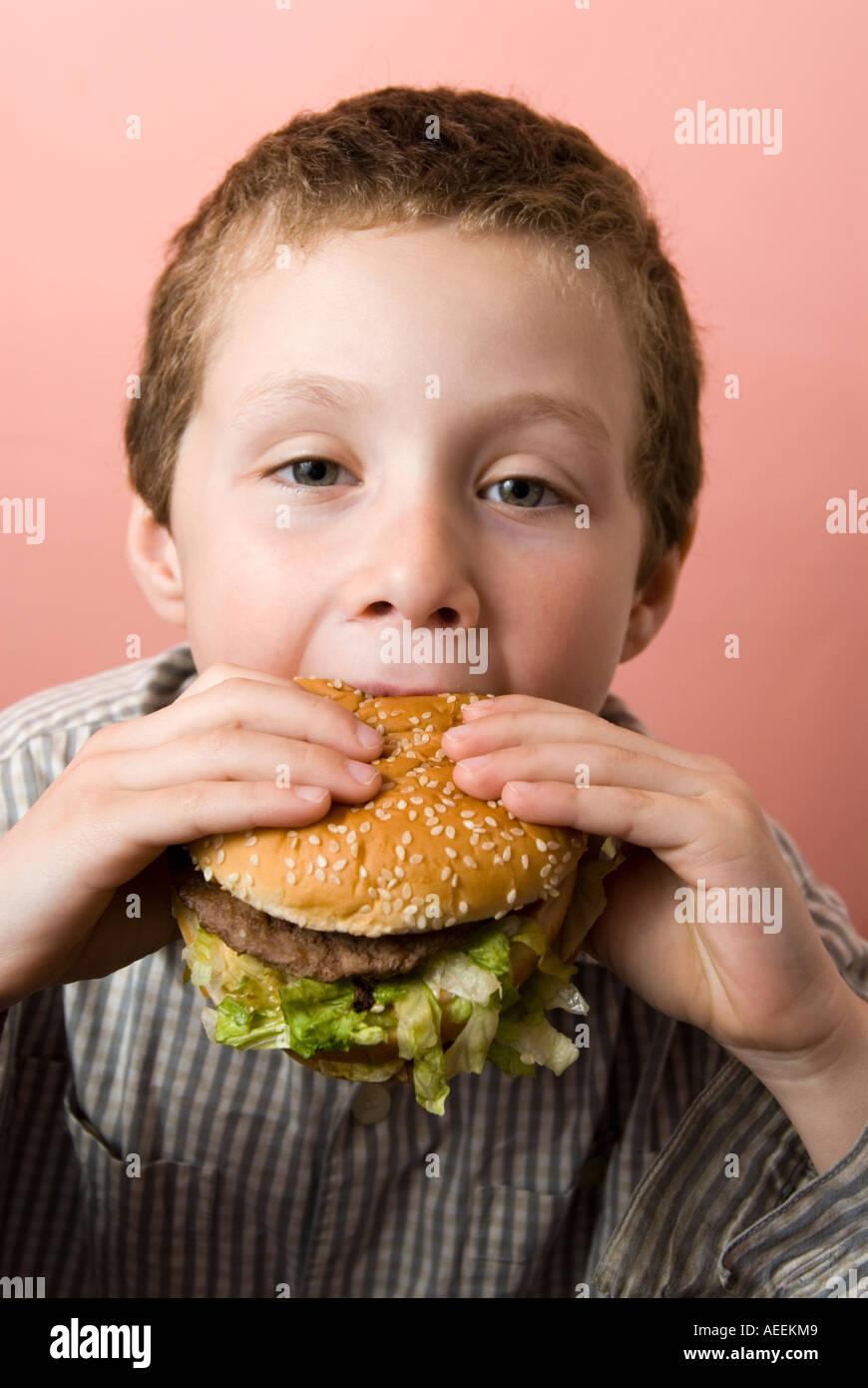 Boy eating McDonald's Big Mac burger, England, UK - Stock Image