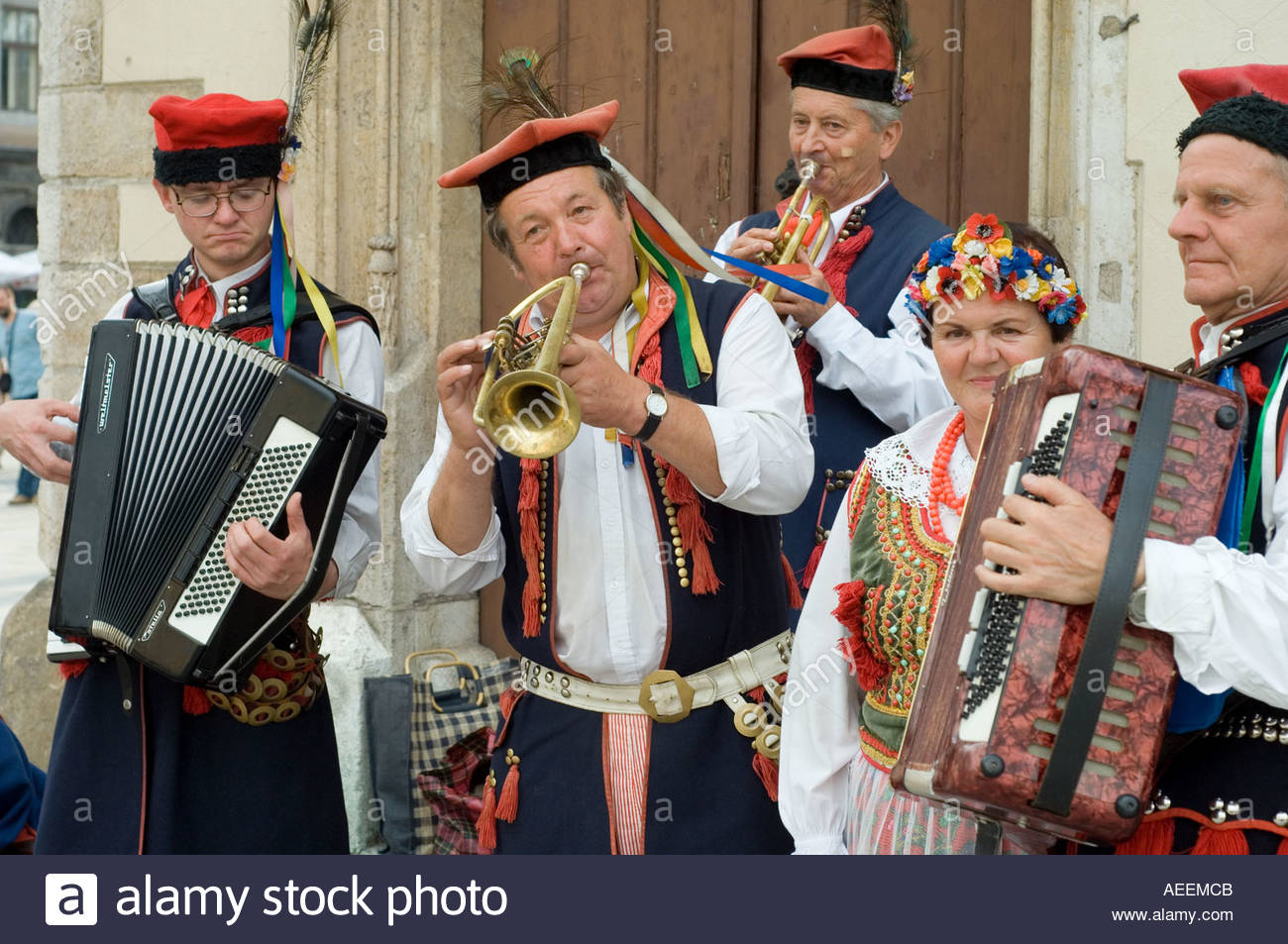 Musicians in traditional dress play Polish folk music for tourists in Krakow - Stock Image