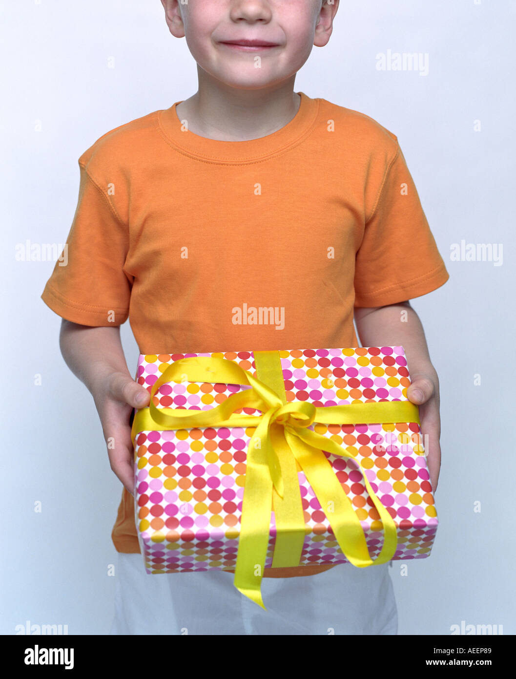 Little Boy With Colorfully Wrapped Birthday Present In His Hands