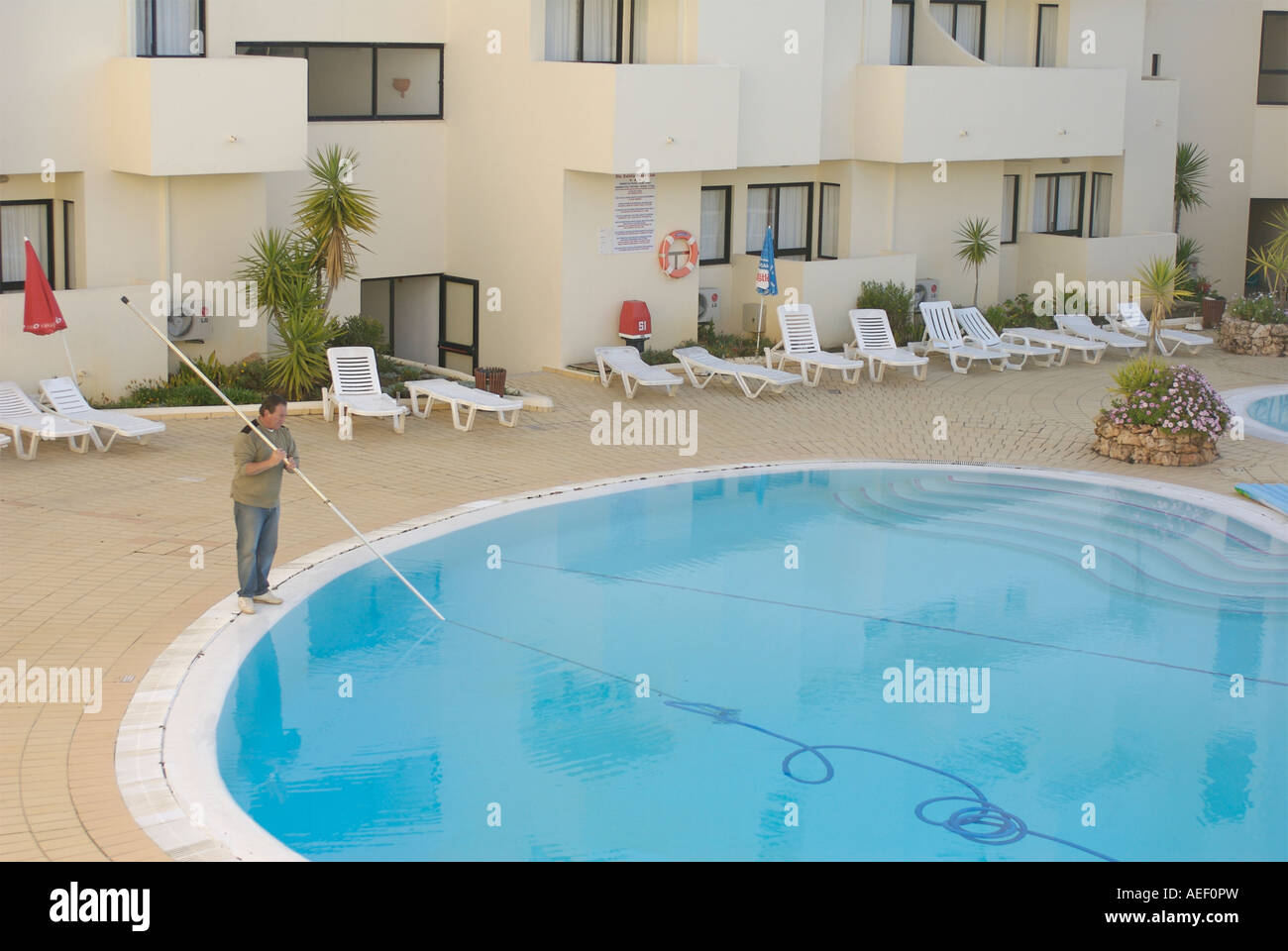 Man cleaning a hotel swimming pool in albufera portugal ...