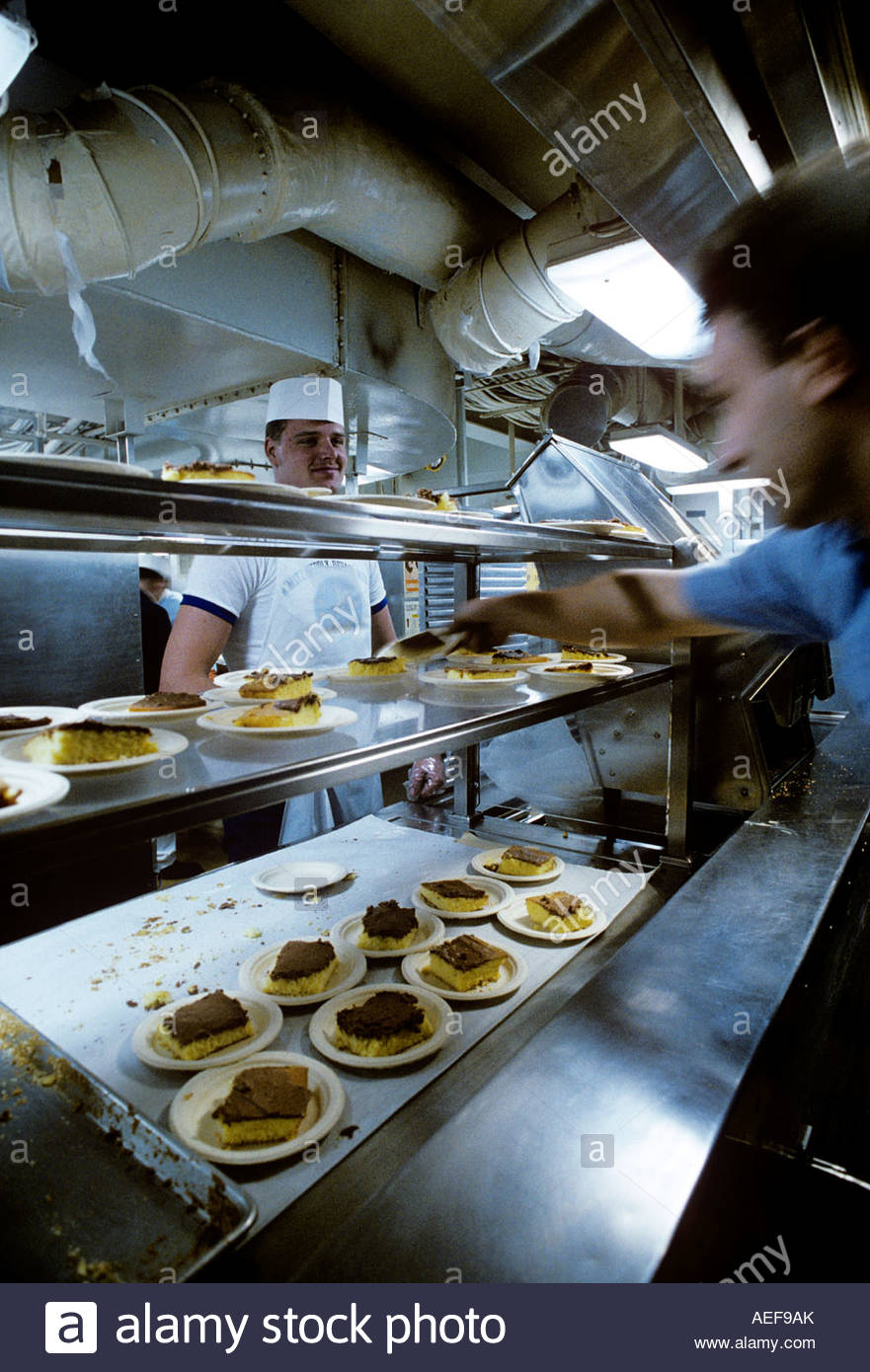Would you like some cake sir? Yellow cake with Chocolate frosting in the  Mess Hall of the USS Nimitz Aircraft carrier - Stock Image