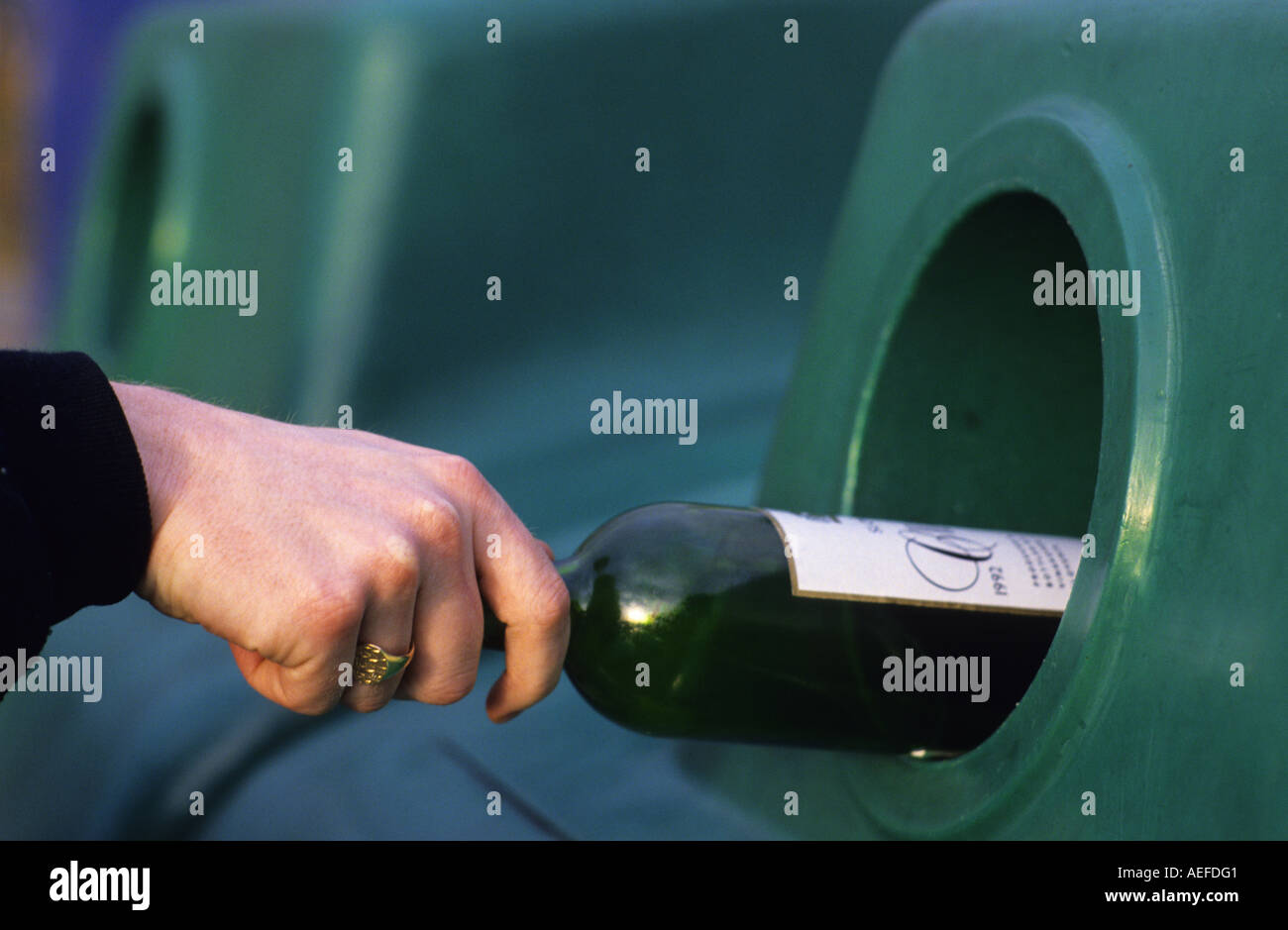 person throwing glass bottle into bottle bank recycling bin - Stock Image