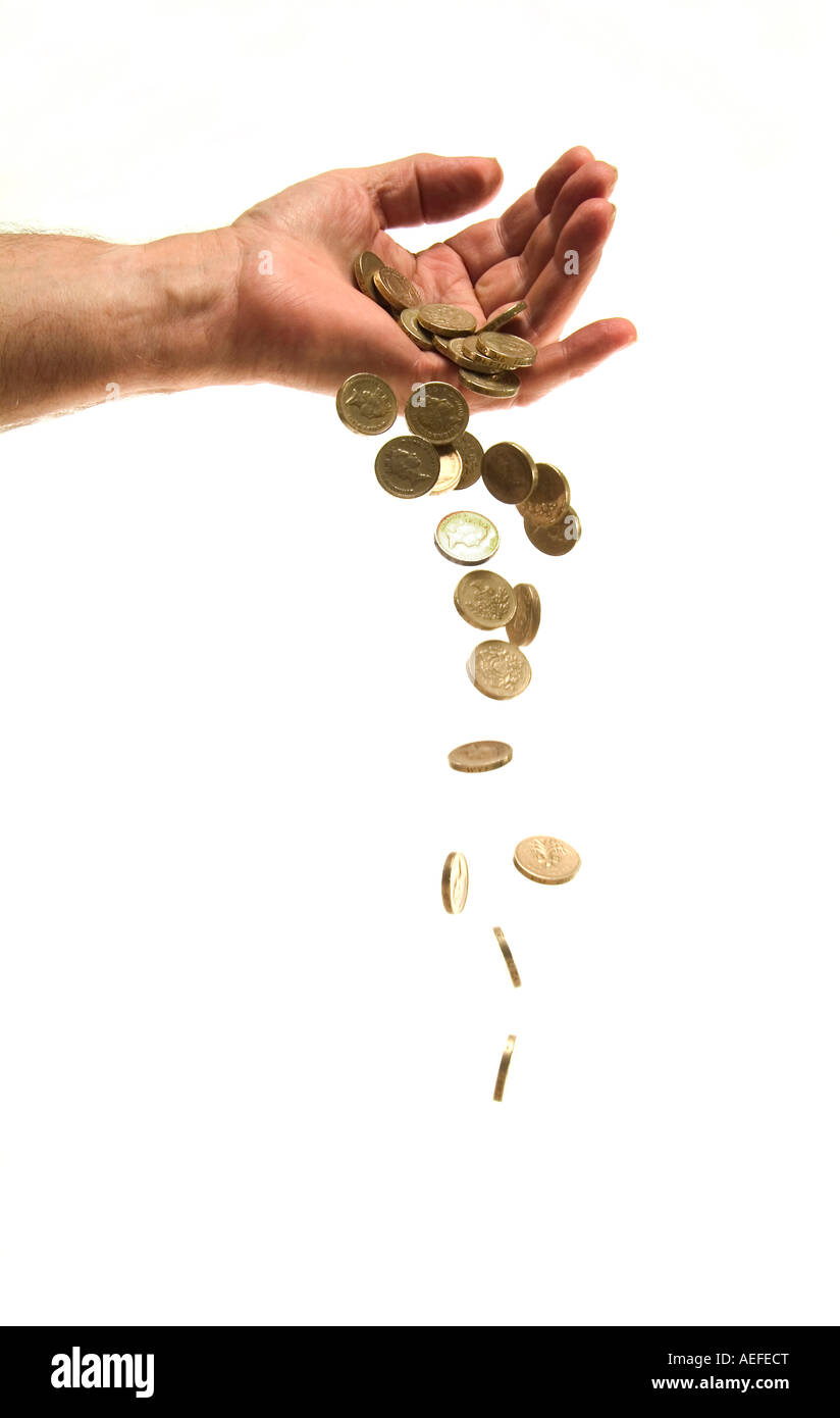 Pound coins falling from hand Stock Photo