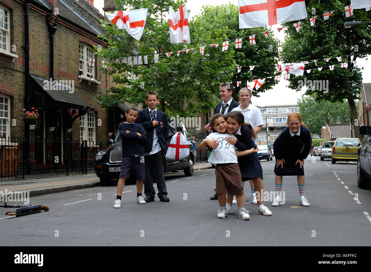 School children of mixed ages on way home from school posing in middle of street at time of World cup final - Stock Image