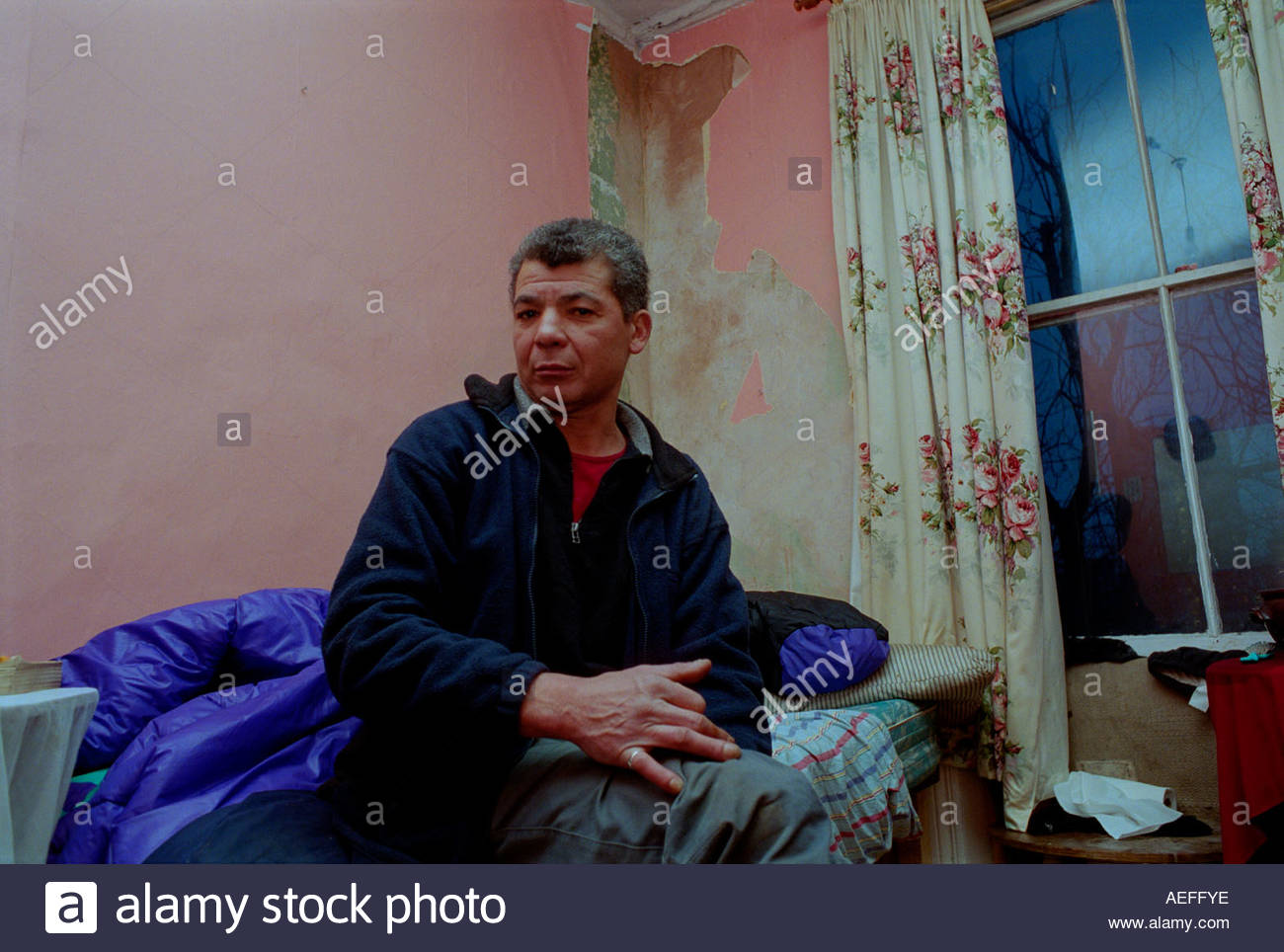 Middle age man living on his own in a room in alternative living accommodation in a London squat. - Stock Image