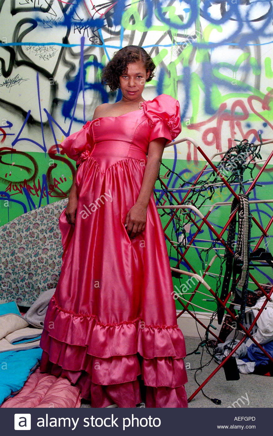 Young woman trying on a pink ball gown in a temporary squat. Stock Photo