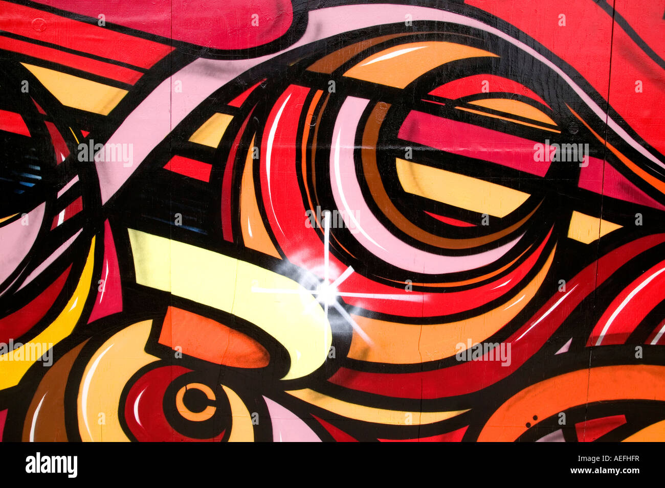Colourful graffiti image sprayed on a wooden wall - Stock Image