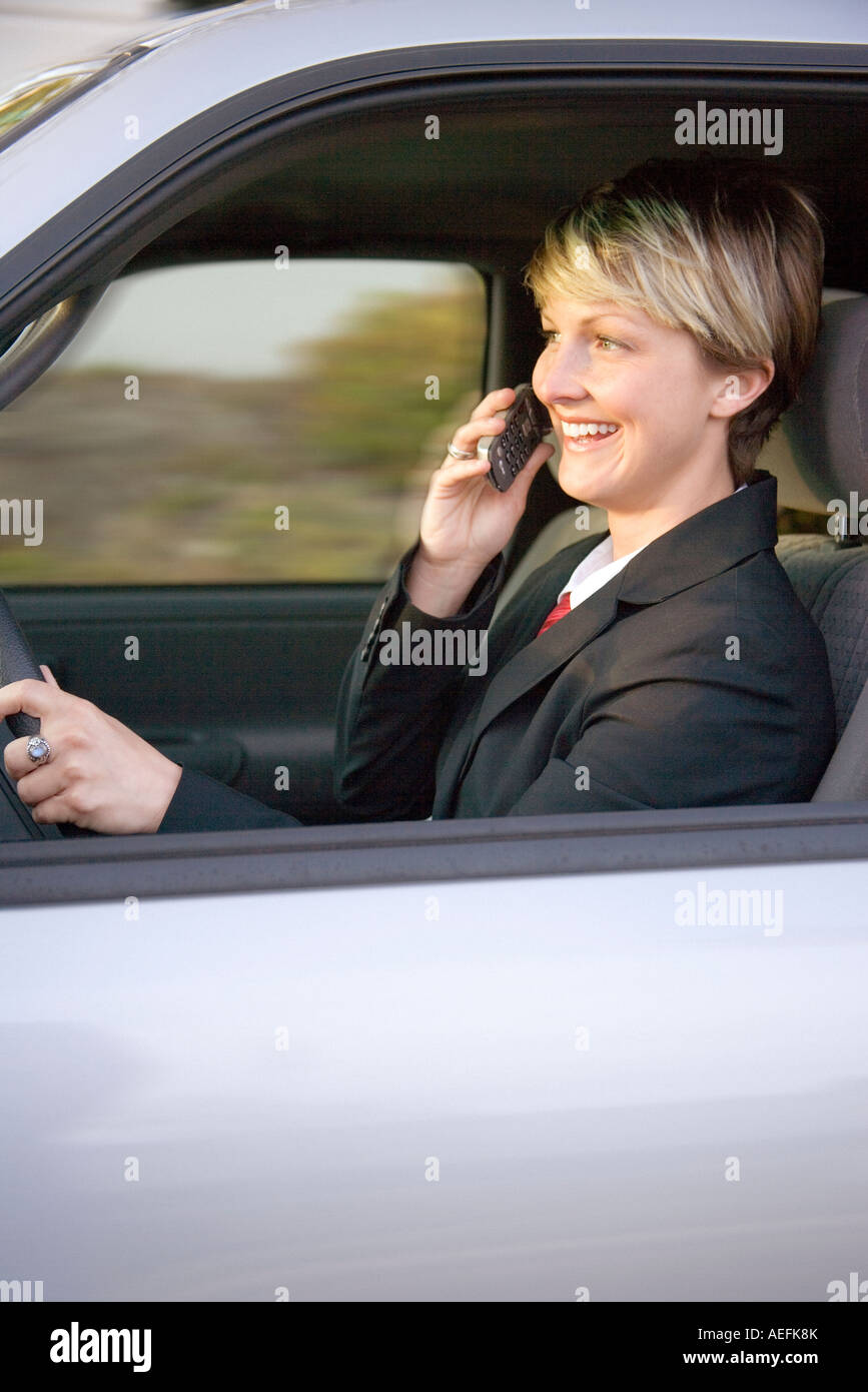 young business woman driving a car and talking on a cell phone Stock Photo