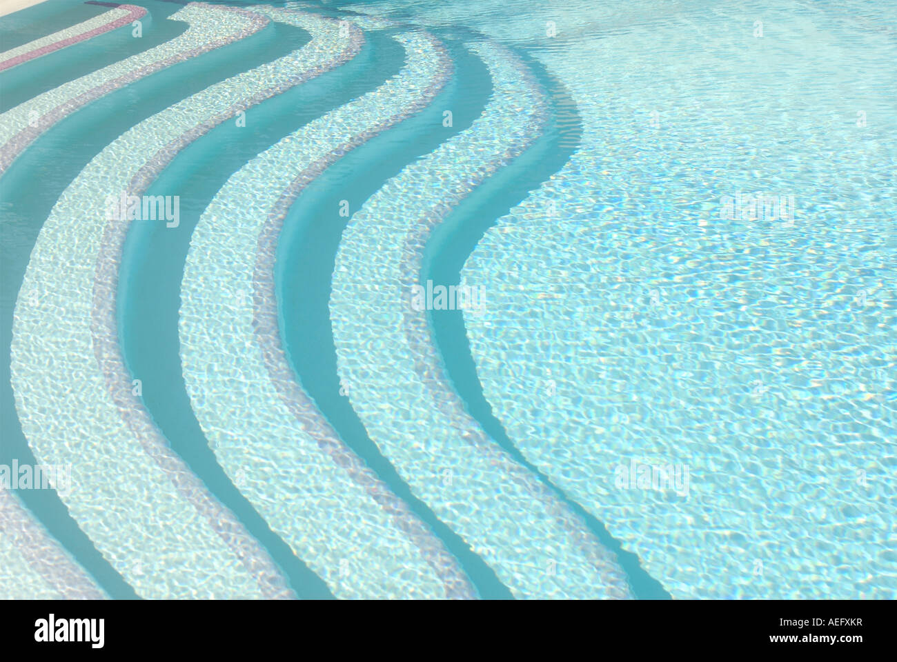 Contemporary patterned bold image of swimming pool steps seen above the water Stock Photo