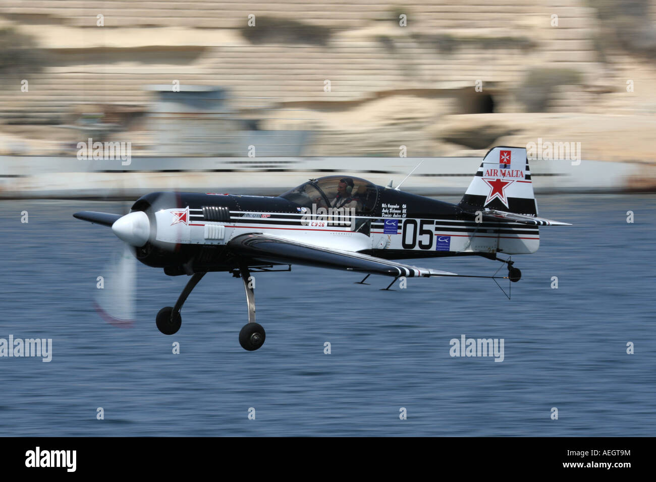 Sukhoi Su-26 single engine aerobatic display aircraft or stunt plane flying fast and low. Slow shutter speed used Stock Photo