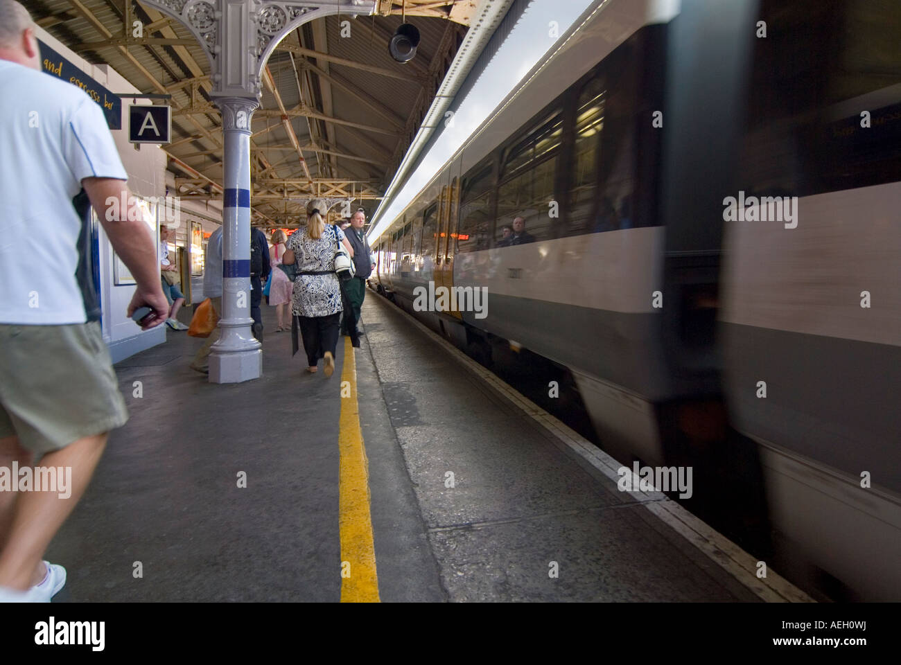 Horizontal wide angle of people rushing to catch a train arriving at the platform. - Stock Image