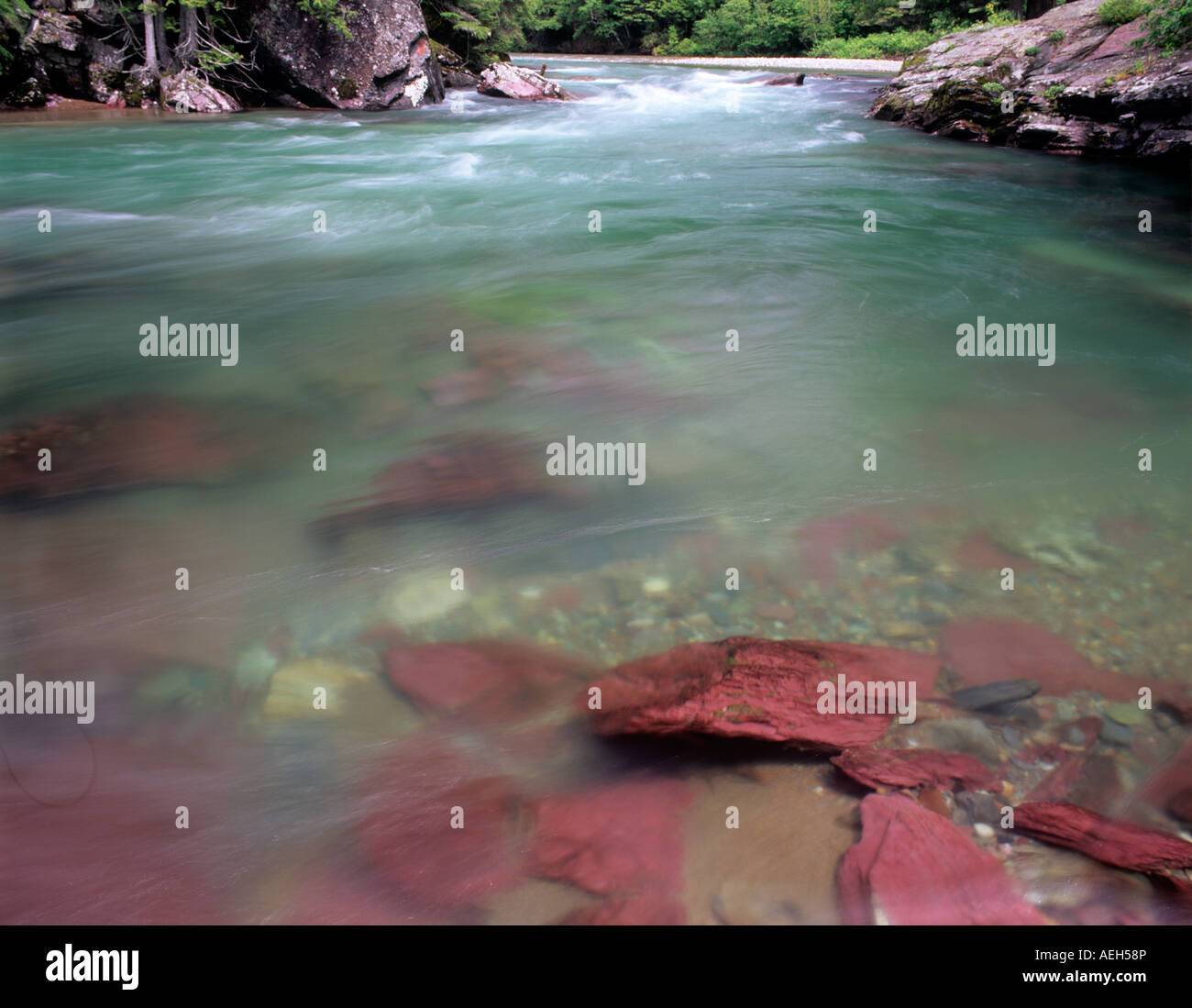 Red rock and green waters of McDonald Creek Glacier National Park Montana - Stock Image