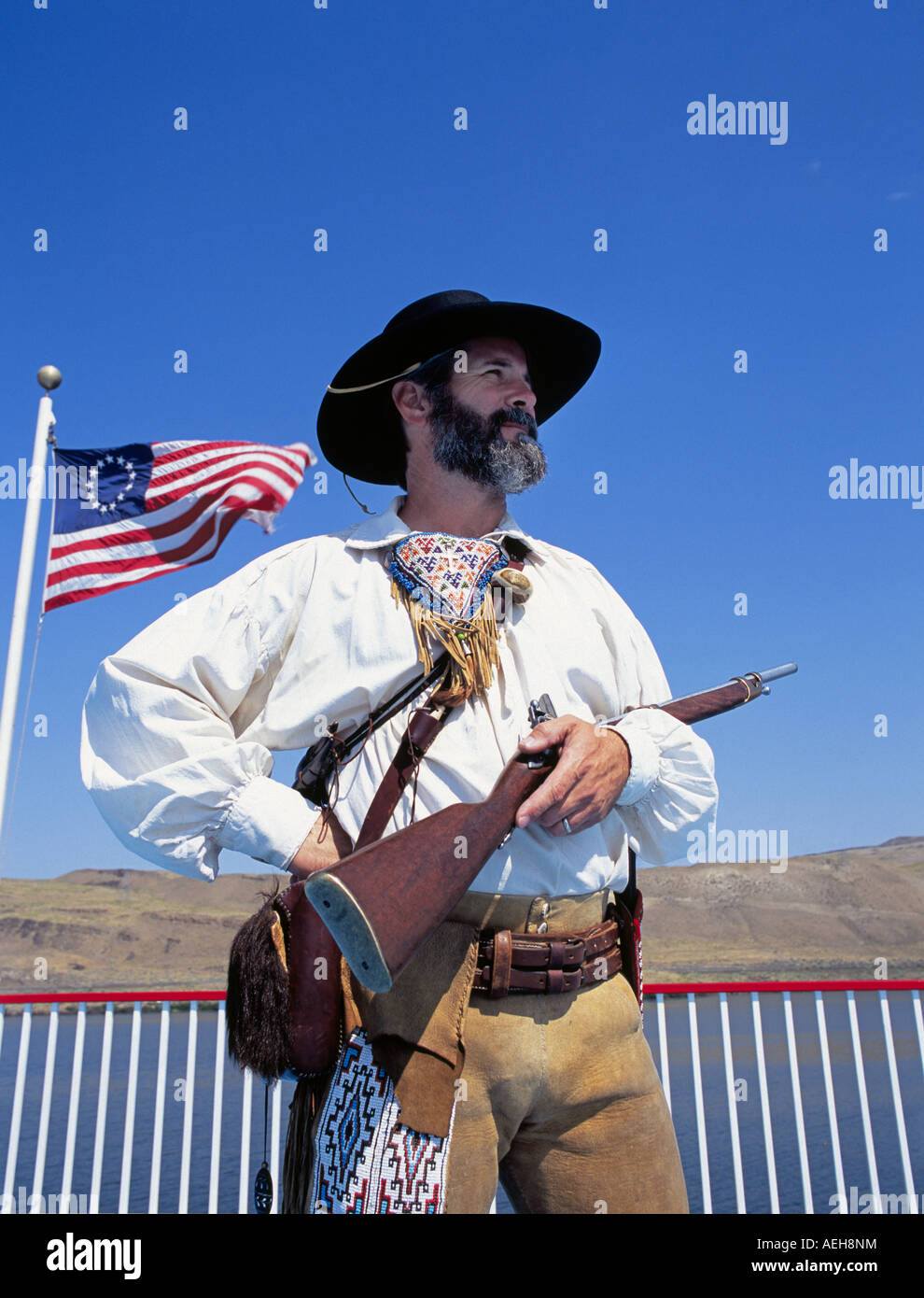 A man dressed as a member of the Lewis and Clark Expedition holds a muzzle loading rifle along the Columbia River, - Stock Image