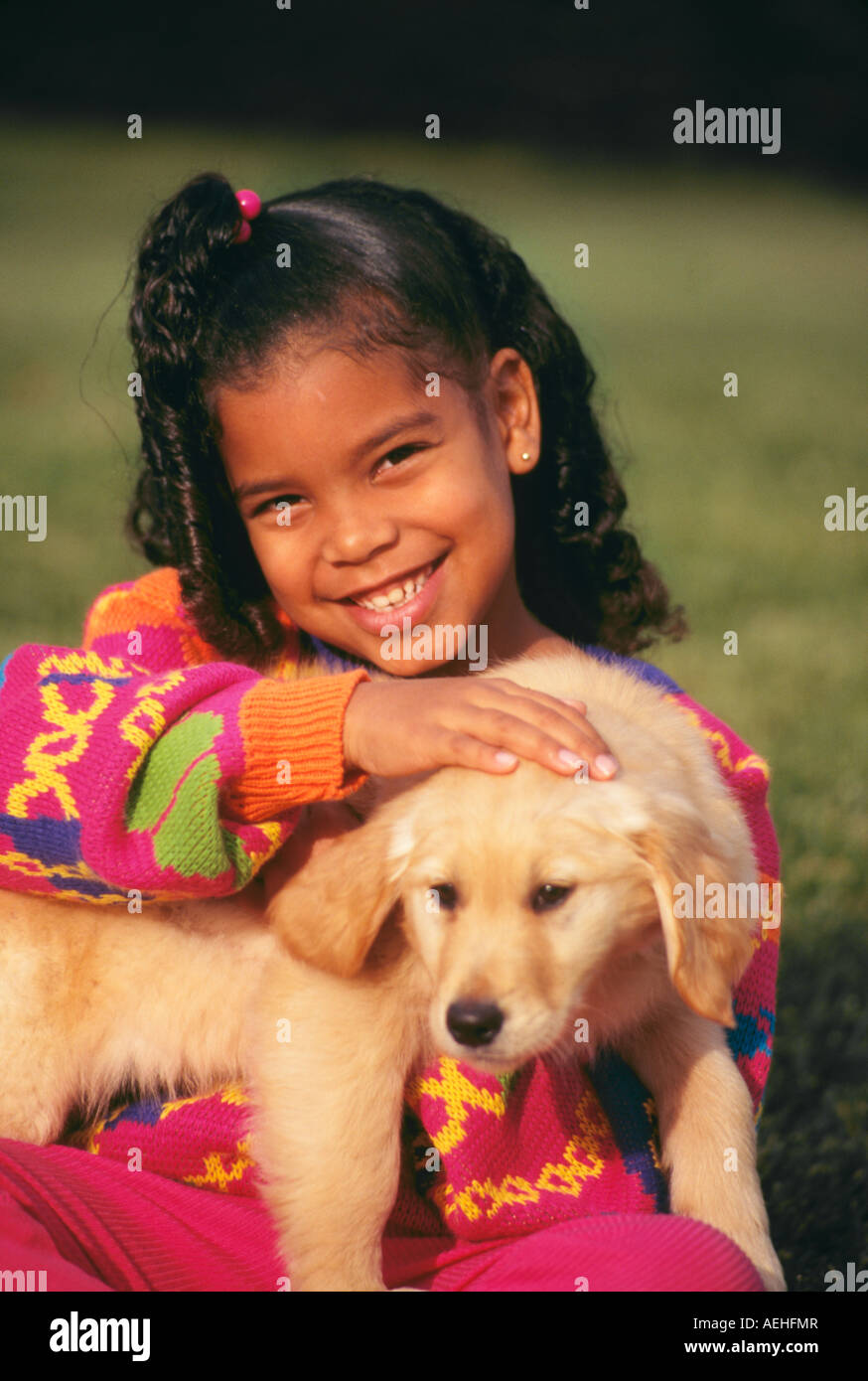 Close up closeup diverse diversity Sweet Girl 7-9 year years old holding puppy smiling portrait cute pet MR  © - Stock Image