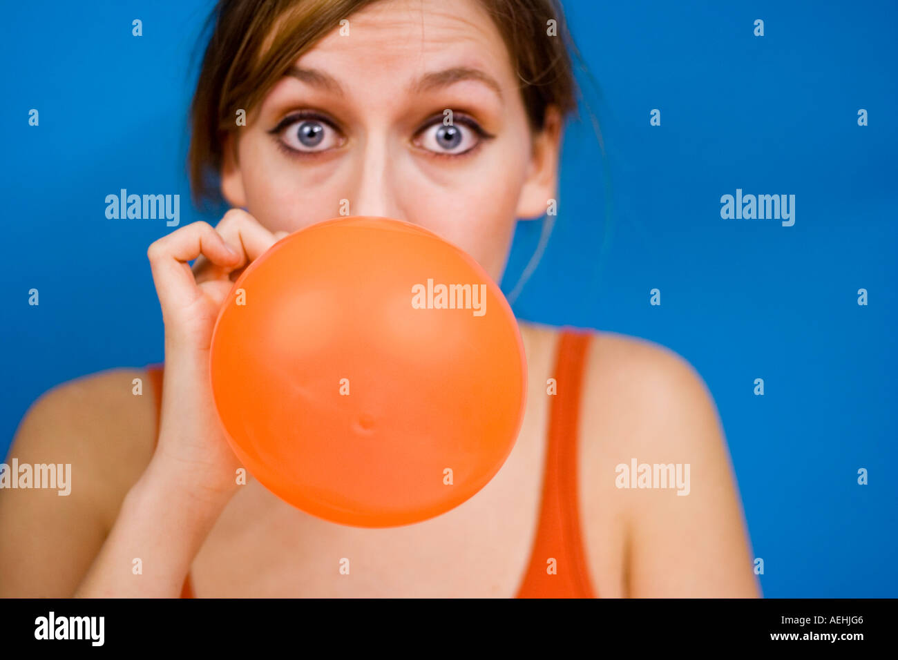 Woman blowing up baloon - Stock Image