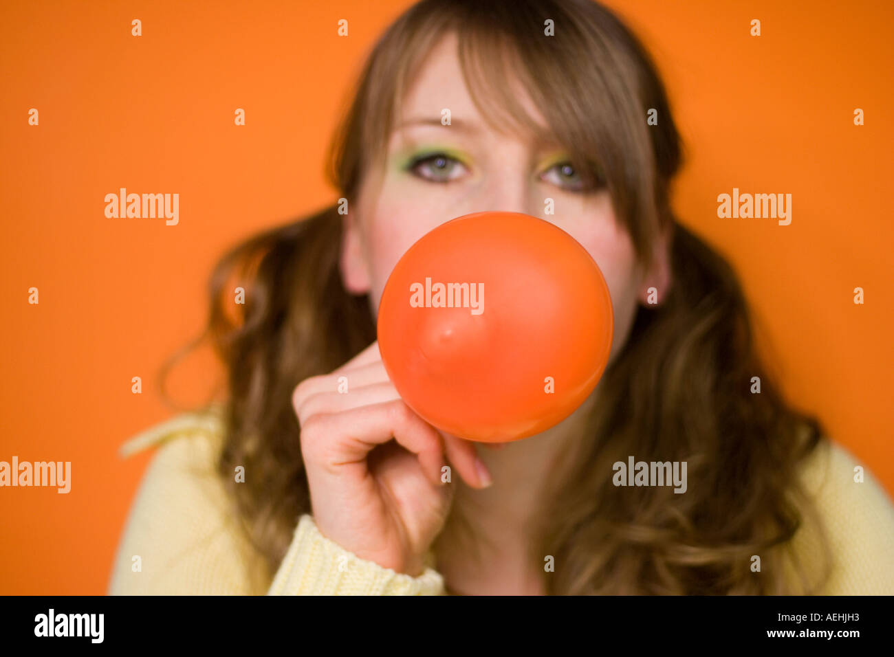 Young woman blowing up balloon - Stock Image