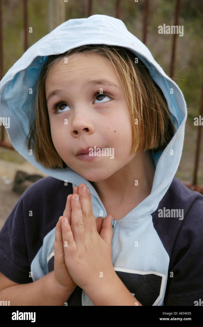 Young white girl pretending to be angelic with the hood of her jacket up over her head and her hands together in - Stock Image