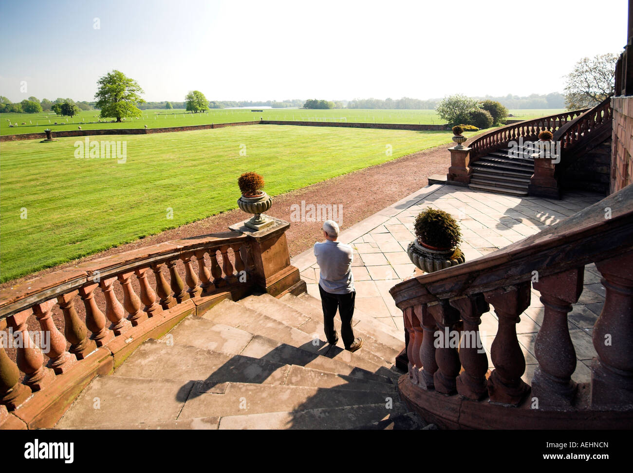 Man standing on the steps of Tabley House, Knutsford, Cheshire, UK - Stock Image