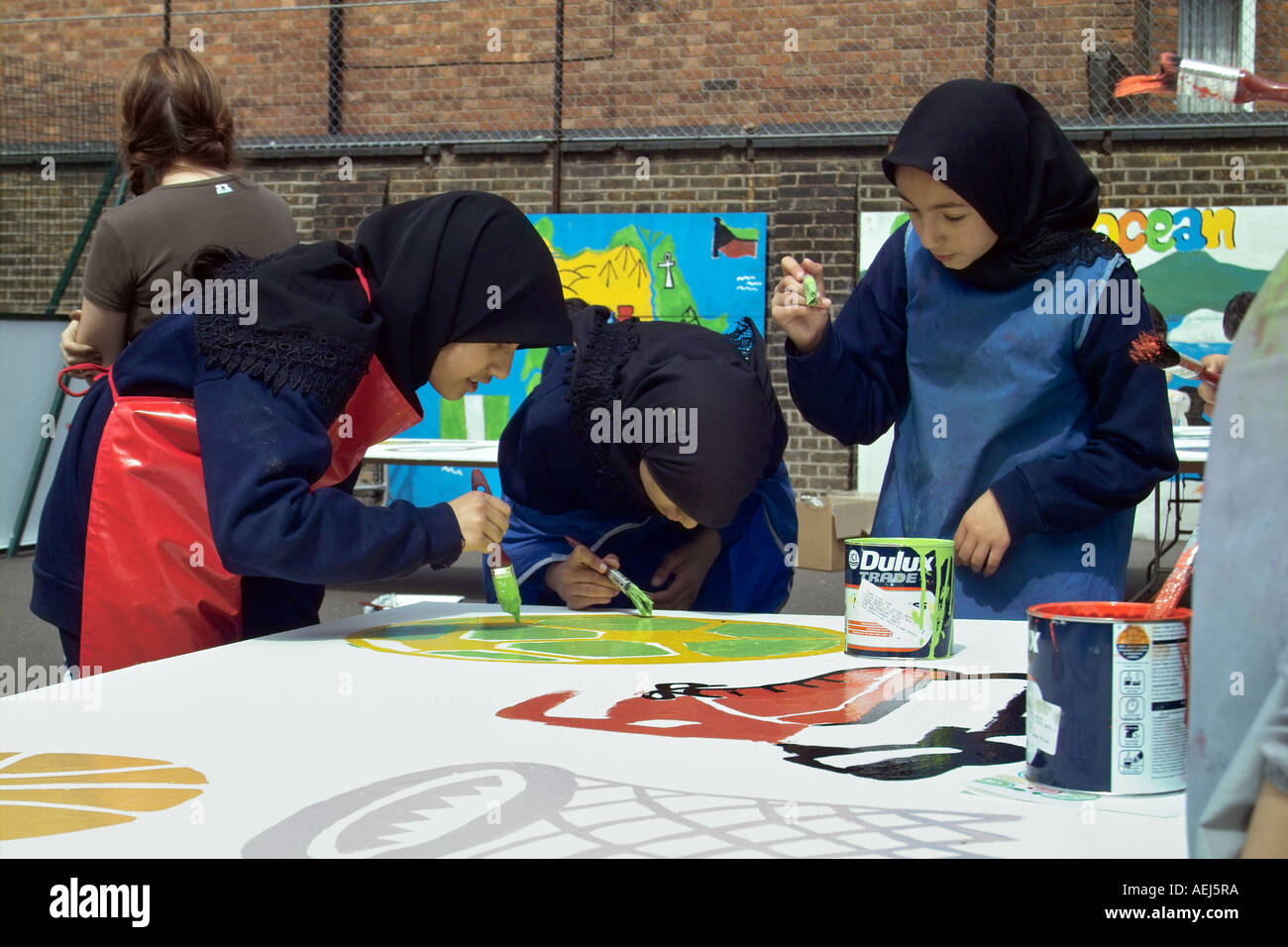 3 muslim school girls wearing hijabs painting designs on large boards - Stock Image