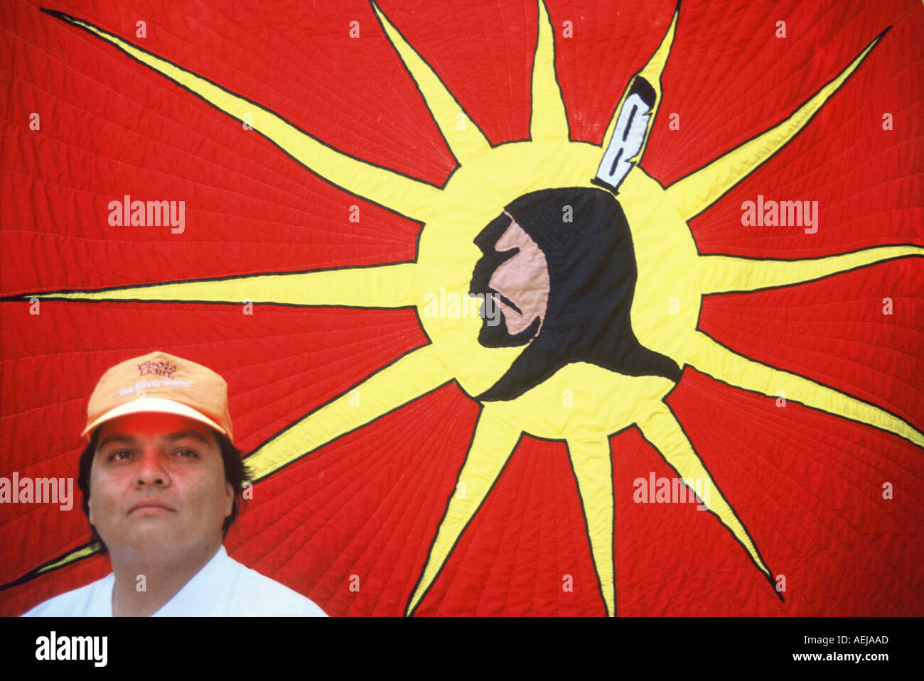 Mohawk man in Oka Quebec canada in front of the symbolic Mohawk flag - Stock Image