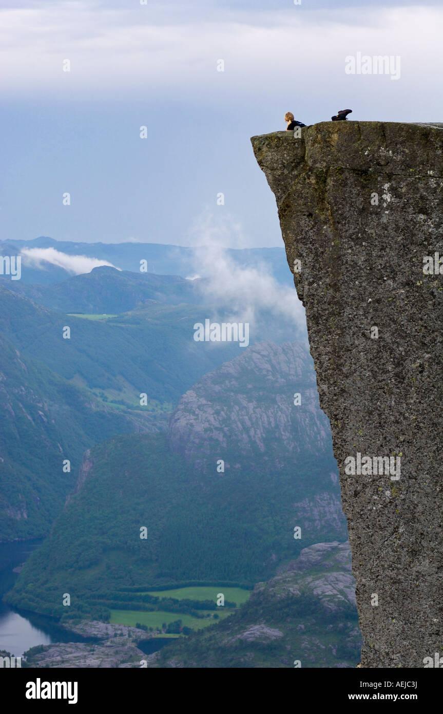 Hiker lying on Preikestolen cliff above Lysefjord, Rogaland, Norway, Scandinavia, Europe Stock Photo