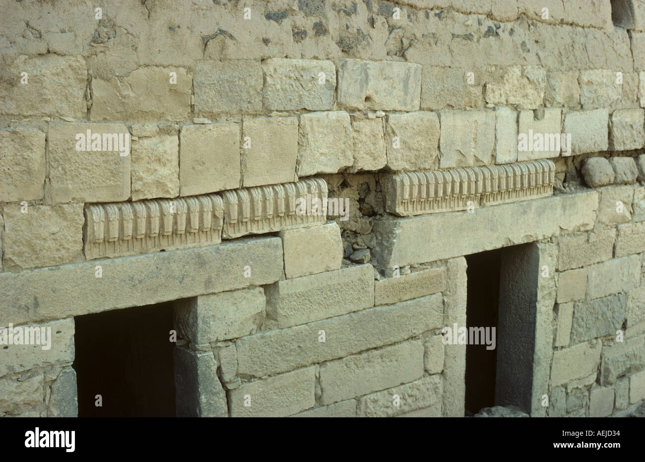Ibex heads and ashlar pecked limestone blocks stolen from nearby temples and used for decoration in building a house old Marib - Stock Image