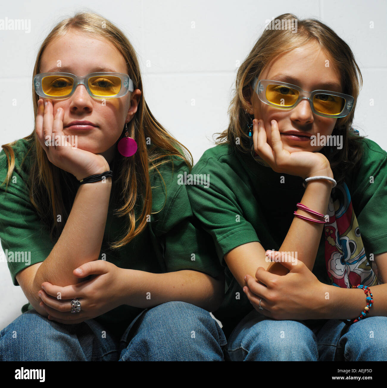 two teenage girls sitting together on white sofa Stock Photo