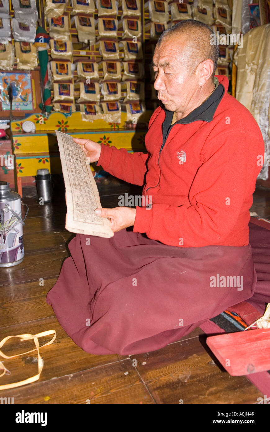Buddhist monk reading a trditional book, Nepal Stock Photo