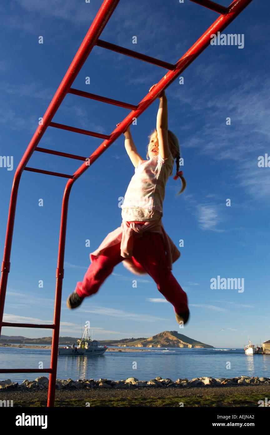 Child Playing on Monkey Bars Karitane Otago South Island New Zealand - Stock Image
