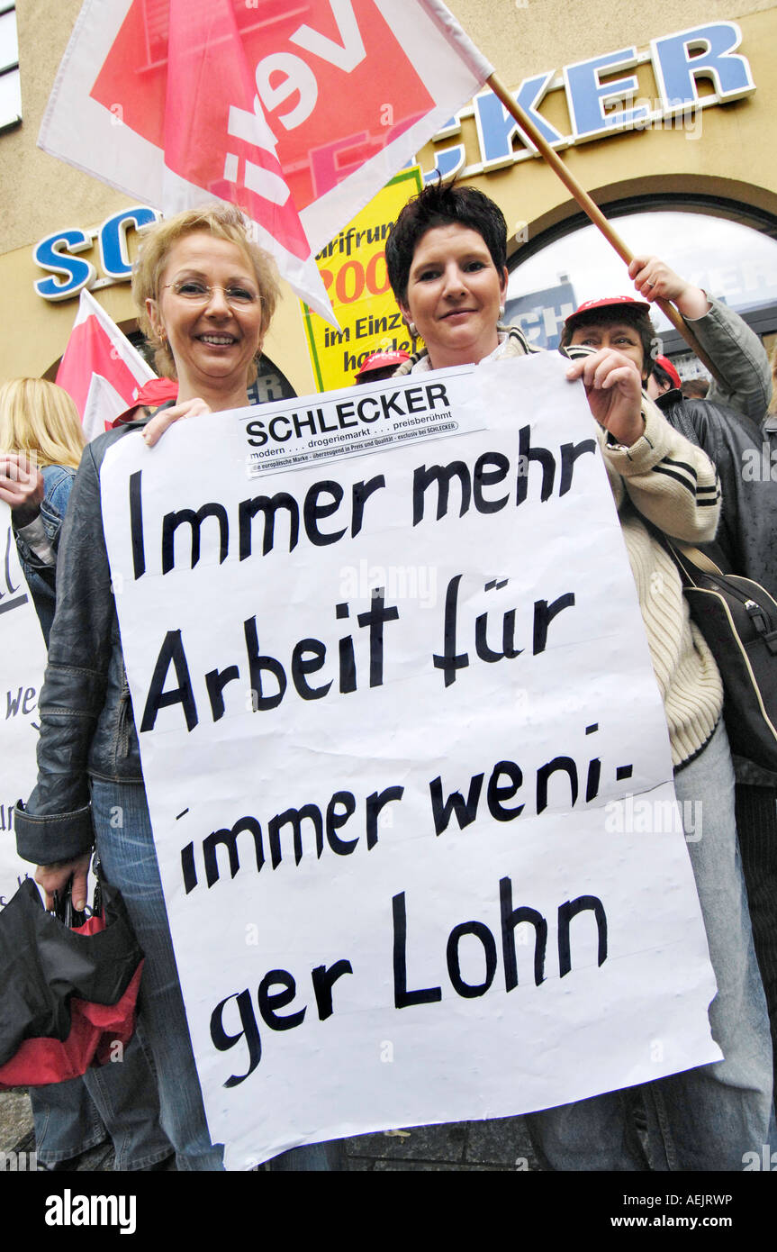 """Sign: """" More work for less wage. Protester in front of Schlecker. Stock Photo"""