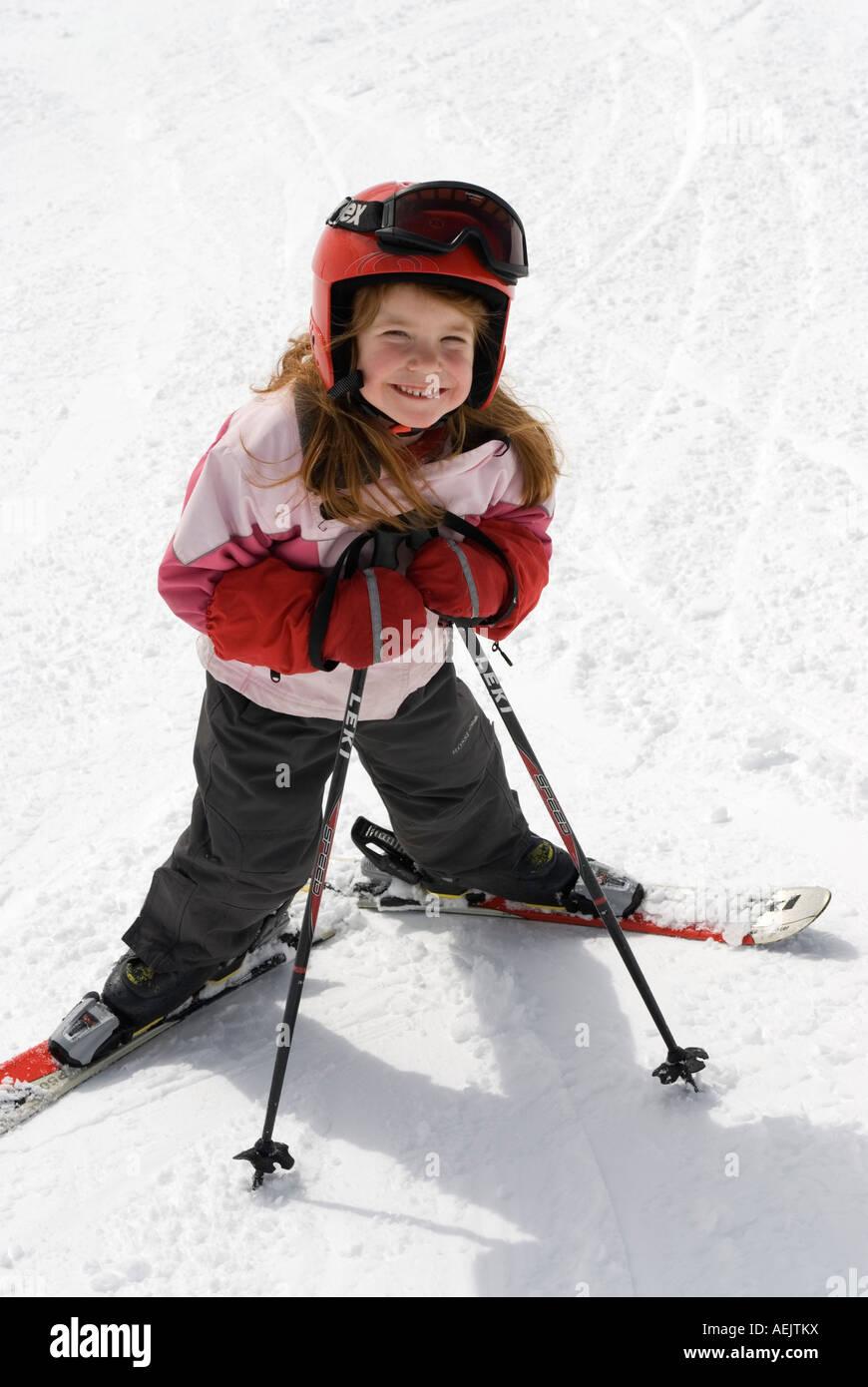 Girl is skiing with helmet skies - Stock Image