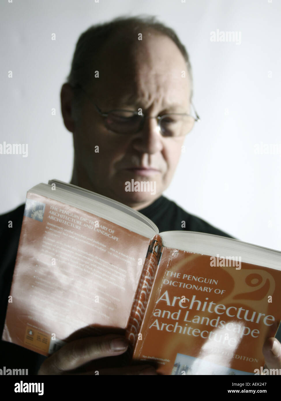 Man aged sixty reading an architecture book