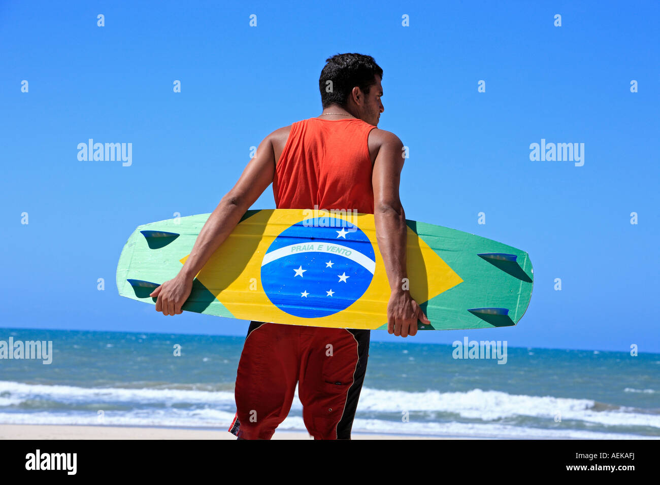 Kite surfer with the brazilian flag painted on the board with 'praia e vento' (beach and wind) instead of - Stock Image