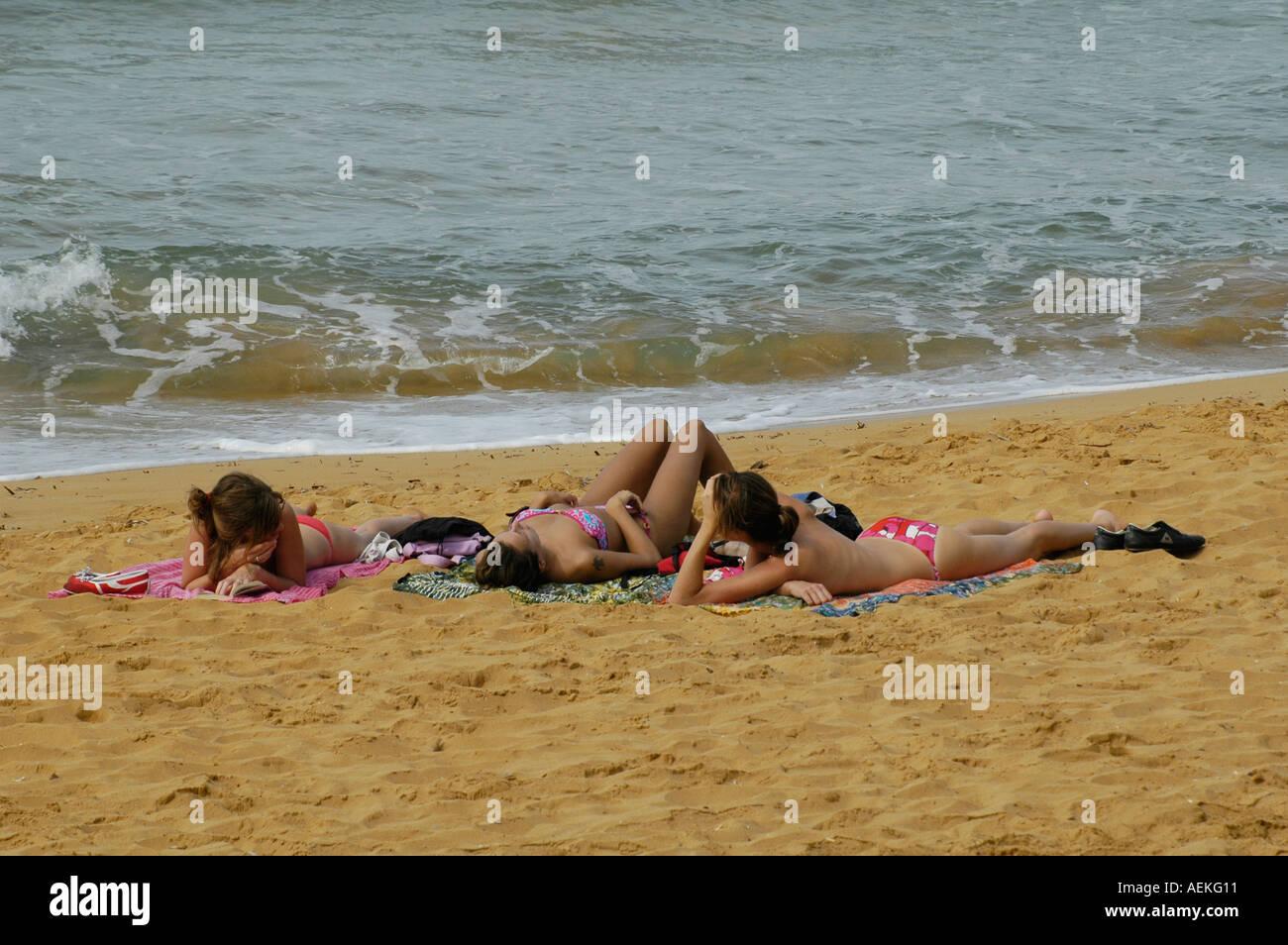 Women sunbathing in Golden Bay one of the few sand beaches on the north west coast of Pierce Newell near Għajn Tuffiena Stock Photo