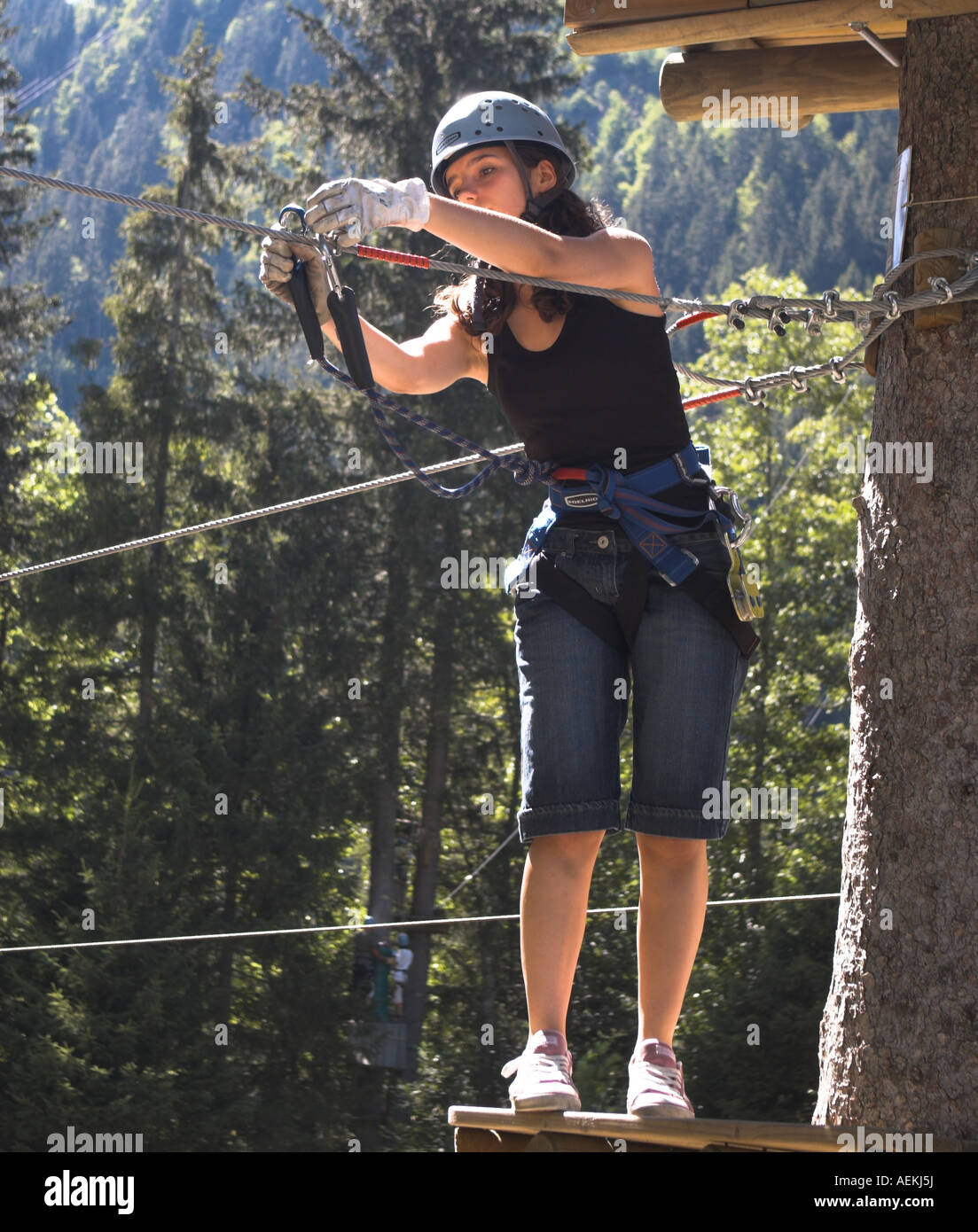 Girl attaches a carabineer clip prior to using a zip wire - Stock Image