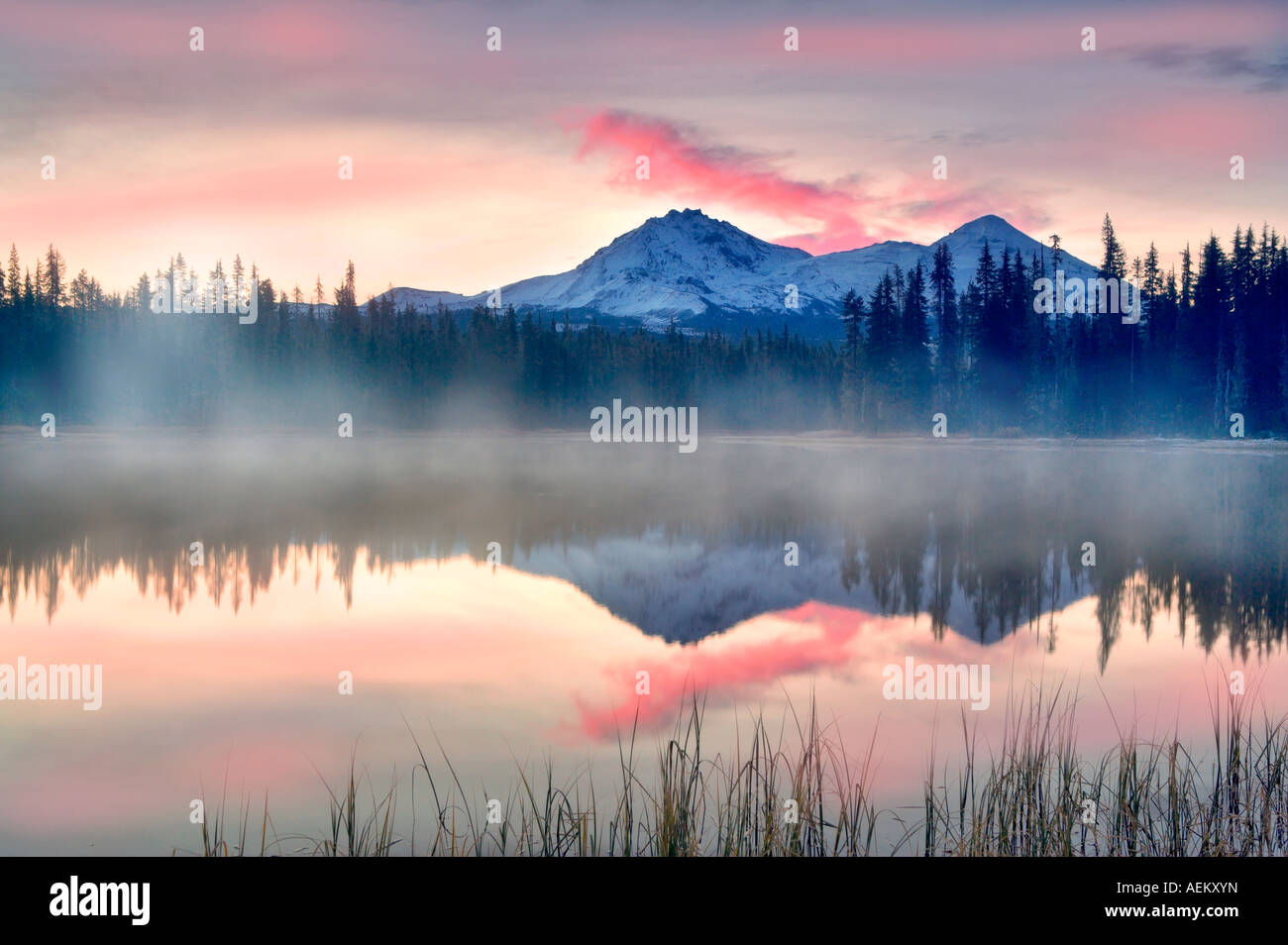 Sunrise on Scott Lake with North and Middle Sister Mountain Central Oregon - Stock Image