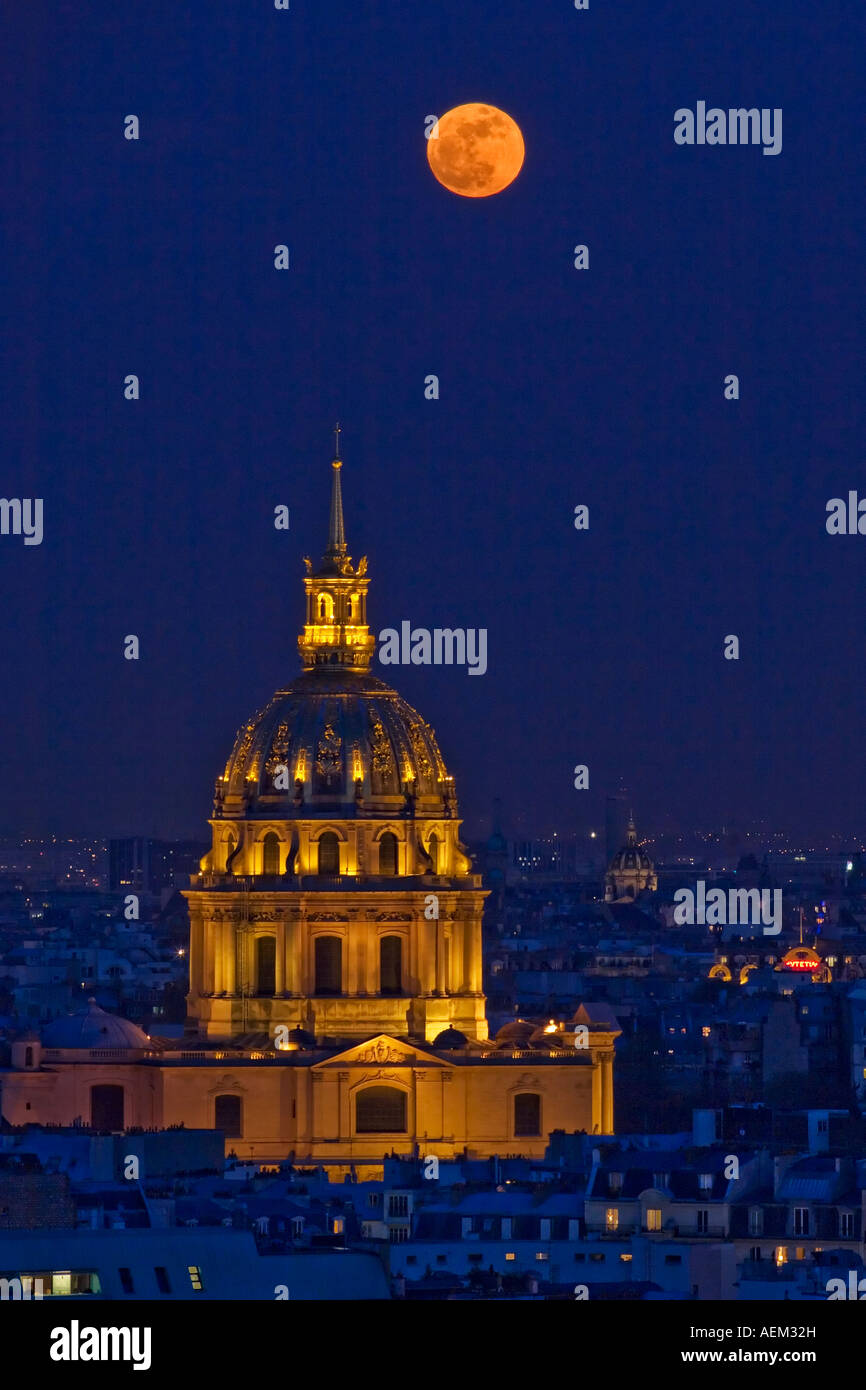 Paris France close up view of Invalides dome and full moon at moonrise - Stock Image