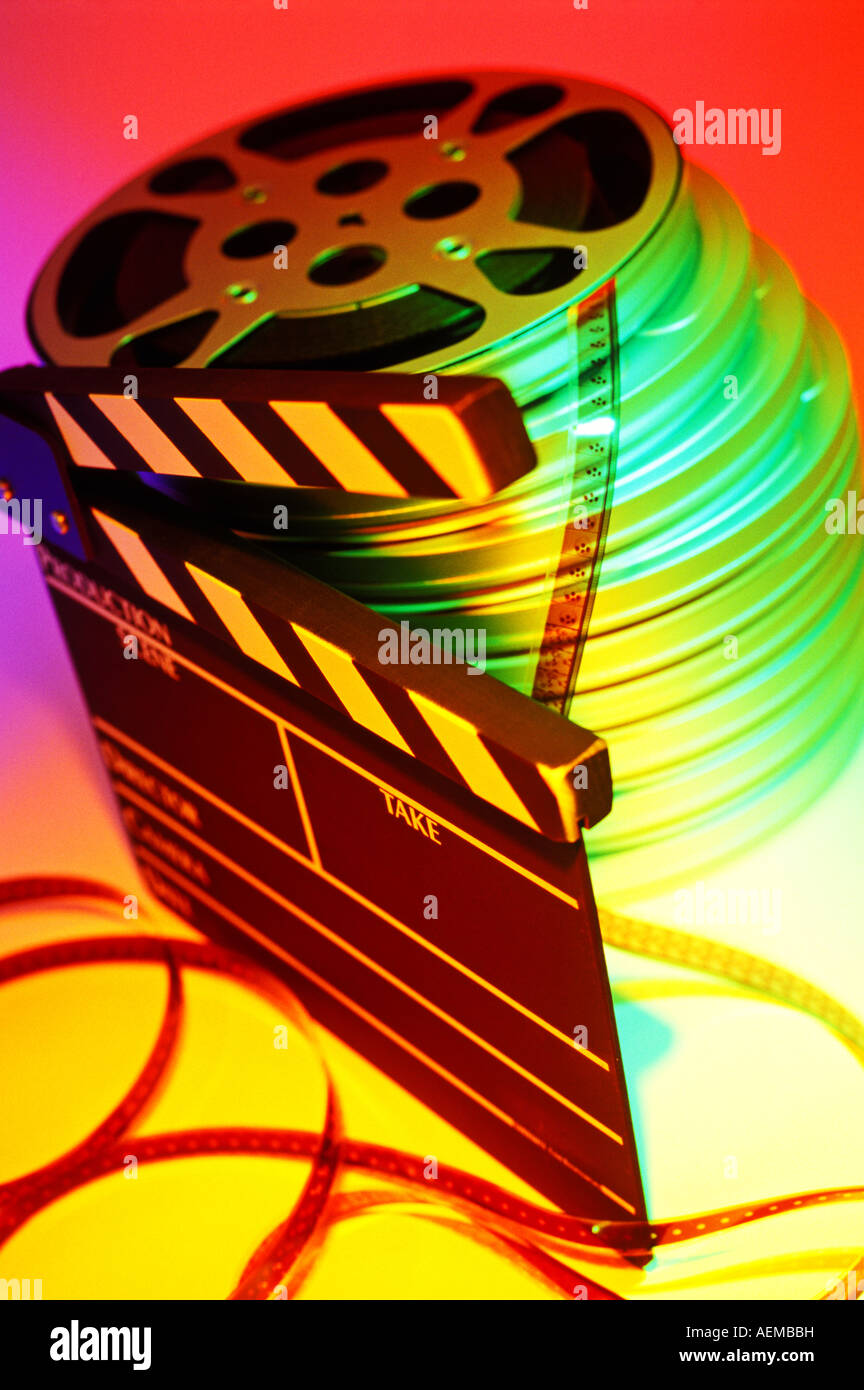Movie film and scene board, with stack of motion picture cans and reels - Stock Image