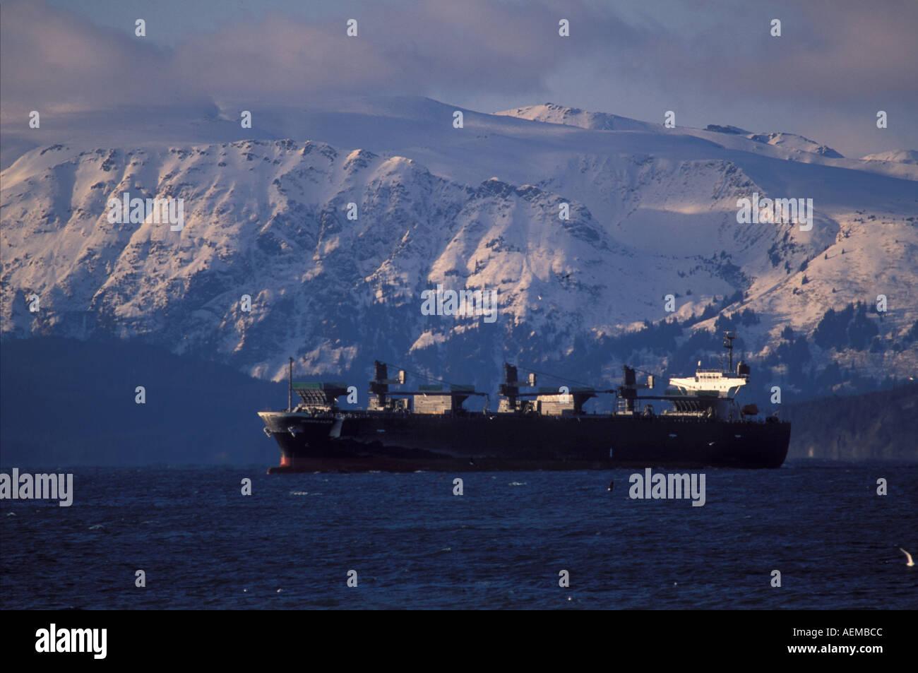 Bulkcarrier cargo vessel anchored waiting for tide change Kachemak Bay with Kenai Mountains winter Alaska - Stock Image