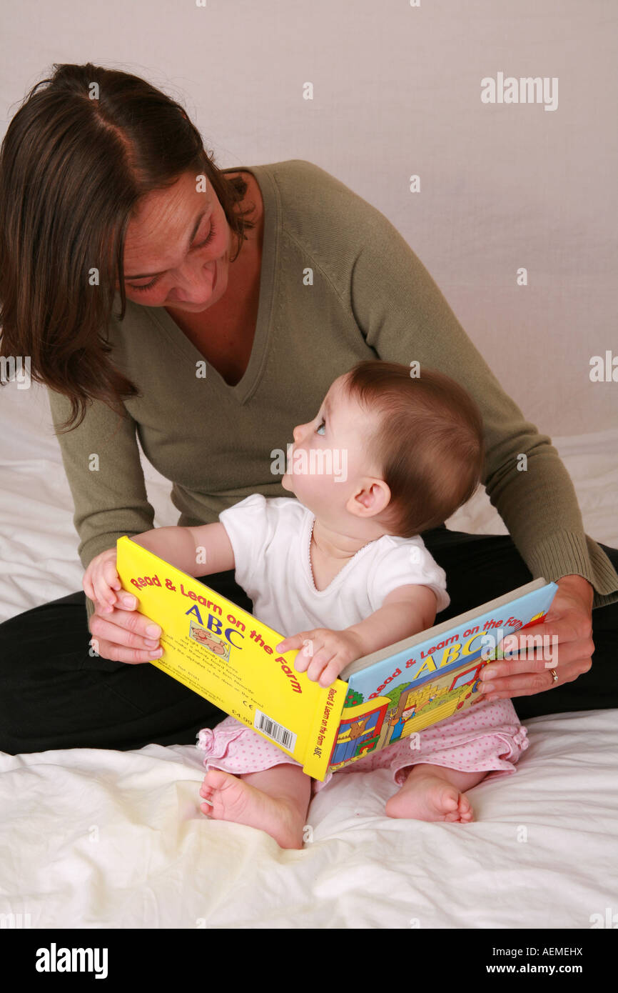 Cute young infant baby child reading a first ABC book at story time looks up to Mother for confirmation praise with - Stock Image