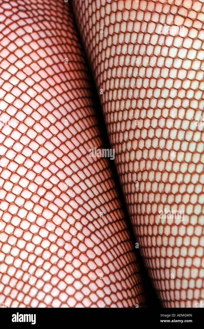 Womans Legs In Fishnet Tights. - Stock Image