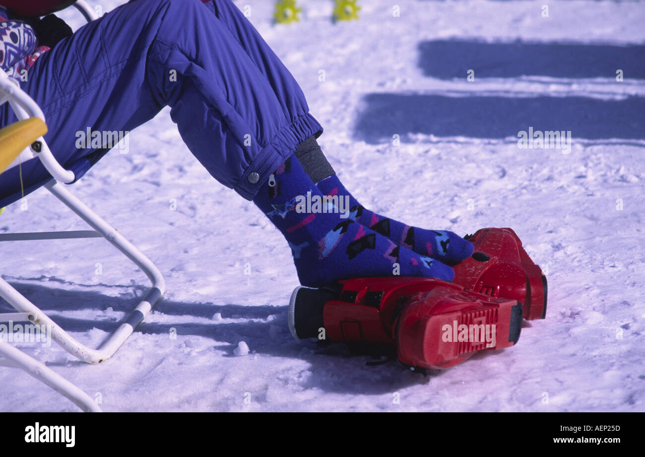 A skier relaxes in the sun and rests their aching feet on ski boots at the French ski resort of Avoriaz, France. - Stock Image