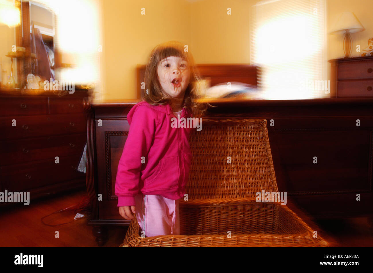 young girl jumps from a basket while playing hide and seek - Stock Image