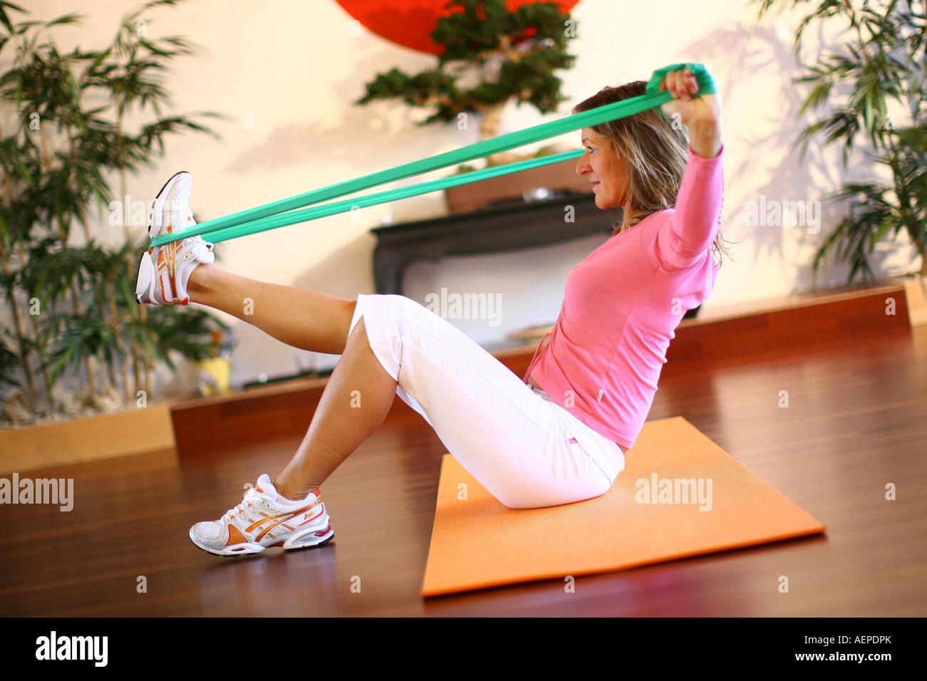 Young woman is training with a deuserband, Junge Frau macht Gymnastik mit einem Deuserband in einem Fitnessstudio - Stock Image