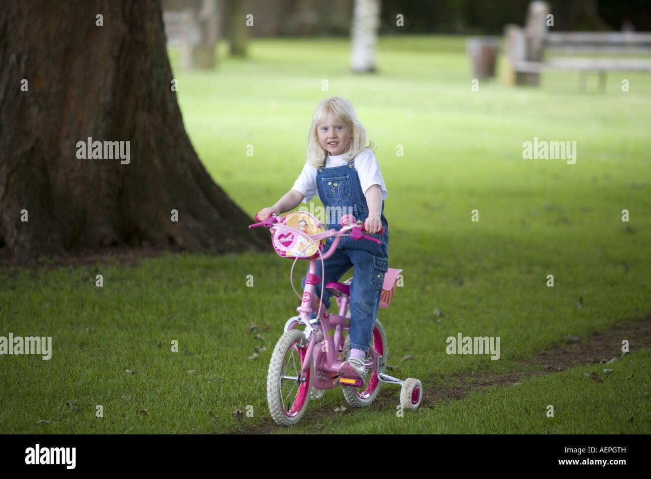 Blonde little Girl on push bike. - Stock Image