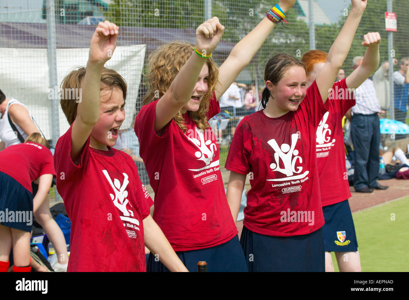 young girls cheering on their team mates at a hockey match - Stock Image